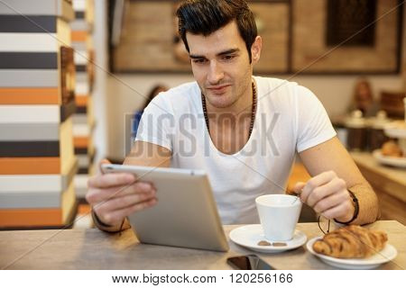 Young man using tablet computer in cafeteria.