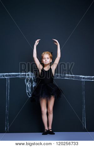 Beautiful girl ballet dancer in black leotard and tutu posing in studio over black background.