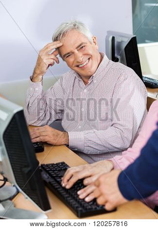 Happy Senior Man At Desk In Computer Class