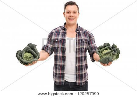 Studio shot of a young farmer holding two whole Savoy cabbages isolated on white background