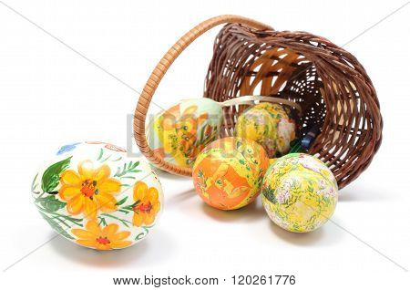 Colorful Easter Eggs In Overturned Wicker Basket. White Background