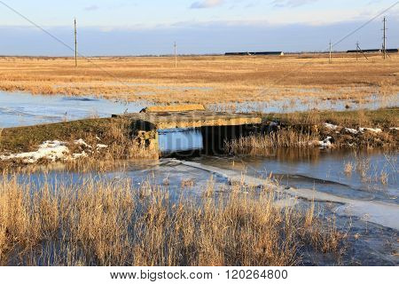 old bridge on rut road in steppe at early spring time