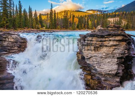 Canada, Jasper National Park. Powerful and scenic Athabasca Falls. Sunset sun illuminates the surrounding mountains