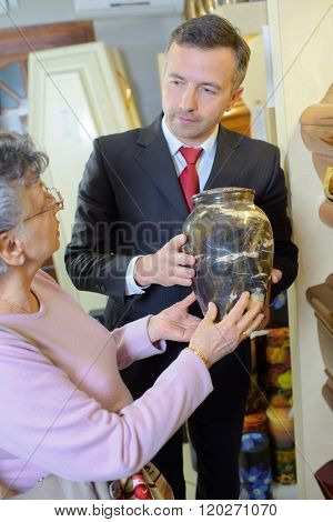 Funeral director with widow choosing urn