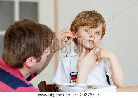 Young dad painting flag on face of little son for football or soccer game. Kid boy fan happy about game of team in champions league. Selective focus. Happy family of two