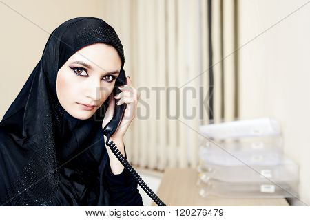 Muslim Woman Talking On A Landline Phone