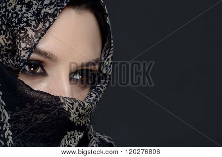 Beautiful Middle eastern woman in niqab on grey background