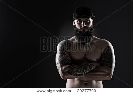 Studio Shot Of Muscular  Man With Tattoo On Dark Background