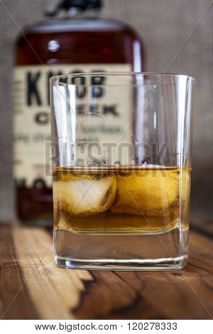 Boulder City Nevada - December 28 : Studio shot of a glass with whiskey and a recognizable label for Knob Creek behind it December 28 2014 in Boulder City Nevada