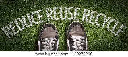 Top View of Sneakers on the grass with the text: Reduce Reuse Recycle