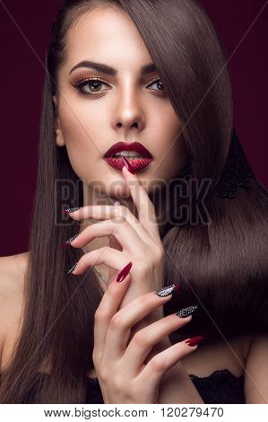 Pretty girl with unusual hairstyle, bright makeup, red lips and manicure design. Beauty face. Art