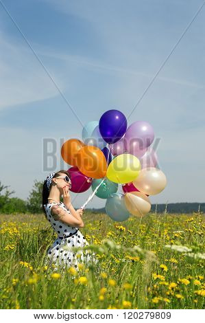 Beautiful Woman In A 50´s Look With A Dotted Dress And Balloons