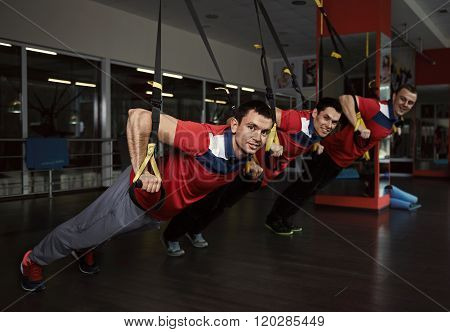 Trx. Gymnastics exercise. Young athletic Caucasian boys training with fitness straps in the gym. ** Note: Visible grain at 100%, best at smaller sizes