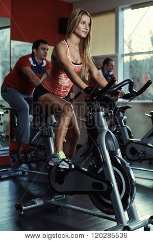 Group of young sporty people at spinning class. Fitness team doing bicycle exercise in the gym. Sport, lifestyle and healthcare concept.