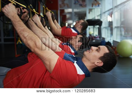 Young muscular men training with sport belts in the gym. Male fitness team doing trx exercise.