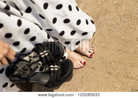 Woman In A White Dotted Dress Holding Her Shoes, Closeup Barefoot