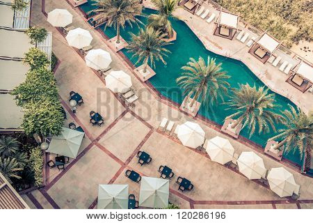 ABU DHABI, UAE - DECEMBER 21: Hotel Poolside with Parasols and Palms. Top view shot on December 21, 2014