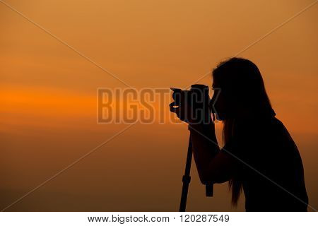 Silhouette Of Woman Shooting With Camera At Sunset
