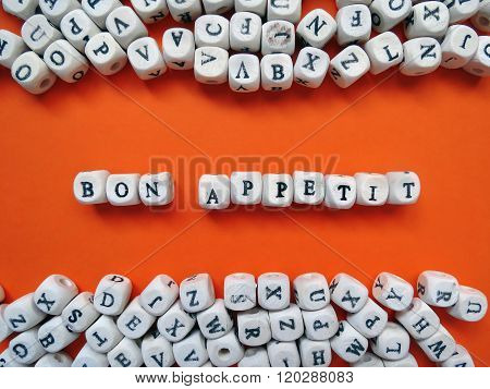 Word Bon Appetit Of Small White Cubes On A Orange Background