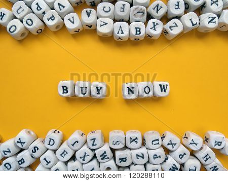 Word Buy Now Of Small White Cubes On A Yellow Background