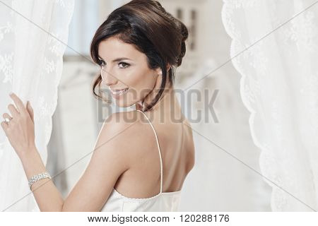 Attractive young bride in white slip, smiling.