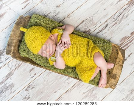 newborn baby in yellow costume sleeping on wooden cot top view