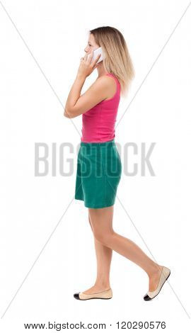 side view of a woman walking with a mobile phone. beautiful curly girl in motion.  backside view person. Isolated over white background. The blonde in a green skirt and red sweater is left on phone.