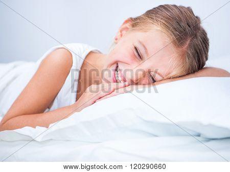 smiling little girl woke up in white bed