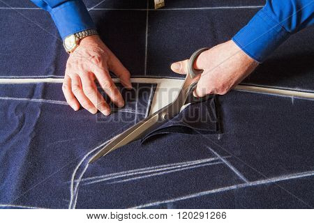 Tailor Cutting Fabric With Scissors.
