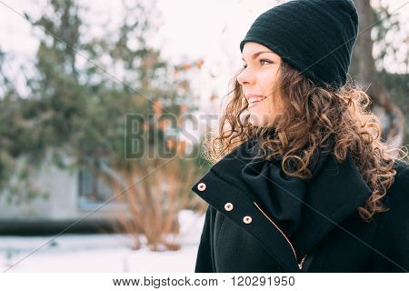 Happy Smiling Girl With Curly Hair In A Coat And Hat In Winter Park