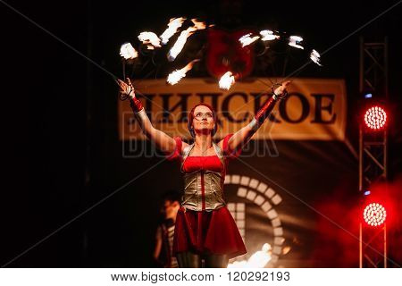 Fire show at night. Young woman stands in front of an audience a