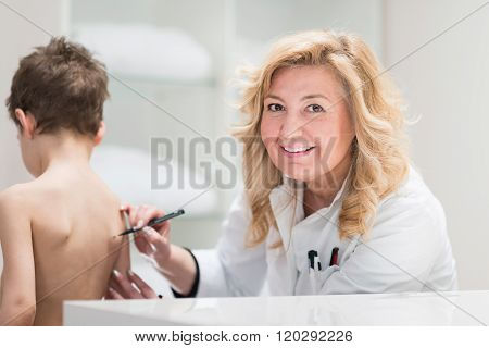 Physical Therapist Examining Posture Of A Little Boy