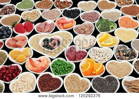 Large body building and health high protein super food with meat, fish, dairy, pulses, cereals, grains, seeds, supplement powders, vitamin pills, fruit and vegetable  selection. Selective focus,