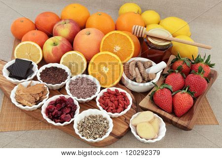 Large antioxidant food and herbal medicine selection for cold and flu remedy also high in vitamin c on an olive wood board over bamboo and hessian background.