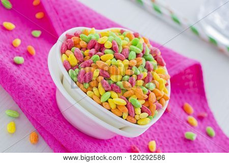 Colorful Rice Cereal on the pink dishcloth with glass of water and straws