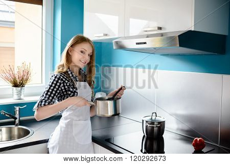 Beautiful Blonde Woman Cooking In The Modern Kitchen.