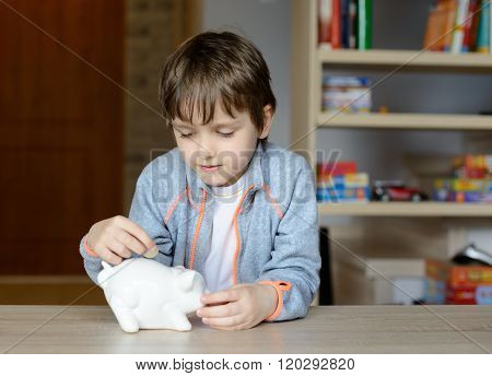 Little Boy Putting His Saving To His Piggy Bank