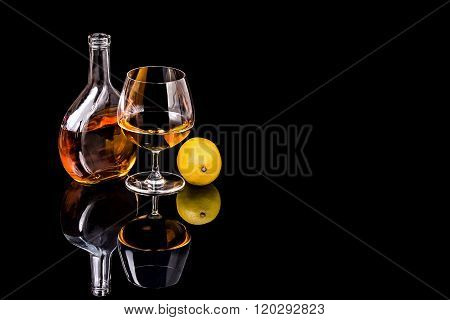 Bottle With Goblet Of Brandy And Lemon On The Mirror Black Surface