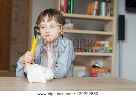 Little boy is going to break his piggy bank - proctective glasses on his eyes