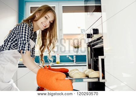 Caucasian Woman Baking A Bread In Kitchen Oven