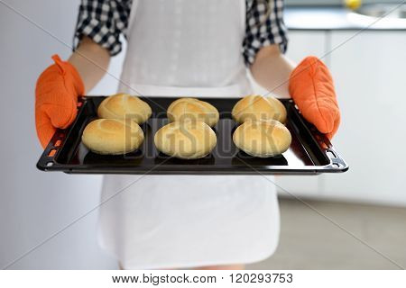 Woman Holding Hot Roasting Pan With Hot, Freshly Baked Bread Rolls