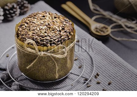 Integral Bread with Sunflower on Black Table, Gray Cloth, Rope and Scissors