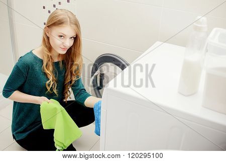 Blond Woman Put Dirty Clothes In The Washing Machine.