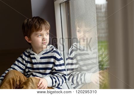Thoughtful Little Boy Sitting By The Window