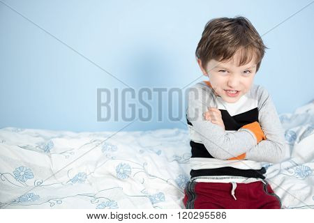 Cute 6 Year Old Boy Sitting On The Edge Of The Bed