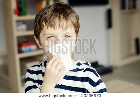 Little boy blows his nose in a paper handkerchief