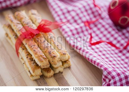Bread Salty Sticks with sesame and flax seeds prepared for New Year's Day with red ribbon and red Ch