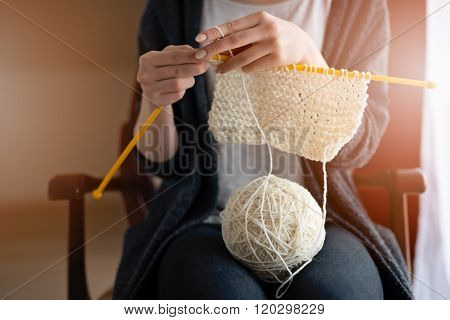 Close up on young woman's hands knitting. Sitting on old armchair near window