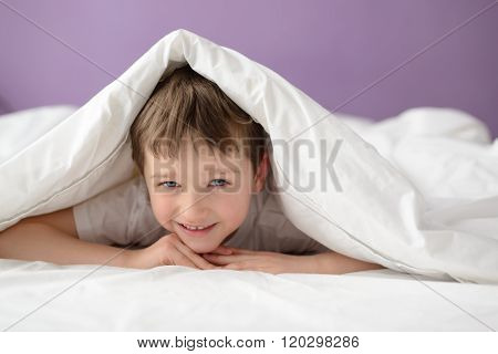 Smiling Boy Hiding In Bed Under A White Blanket Or Coverlet