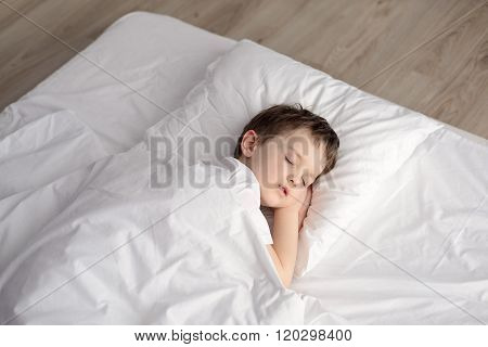 Tired Little Boy Sleeping In Bed, Happy Bedtime In White Bedroom